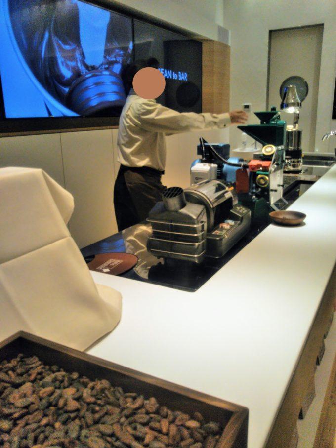 スタッフの方が機械にカカオ豆を入れて粉砕される様子をデモストレーション