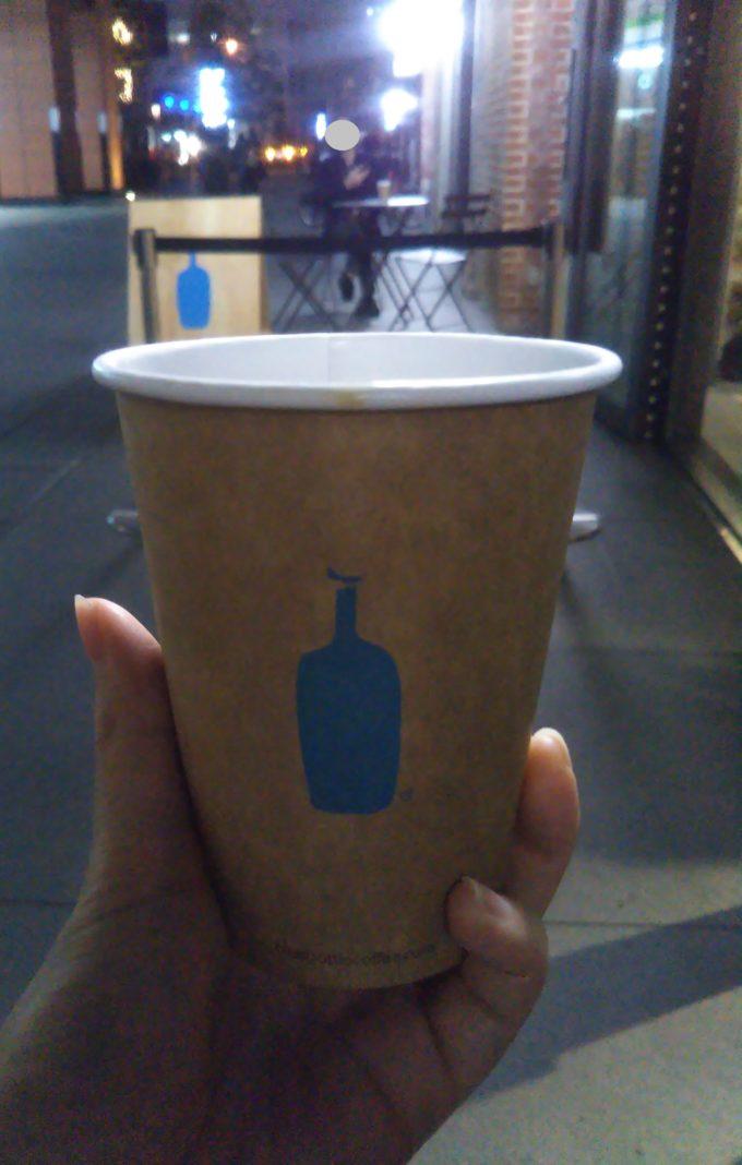 コーヒーボトルを片手に描かれたをブルーボトルのマークを見つめる視線の先にもブルーボトルのマークが見えた